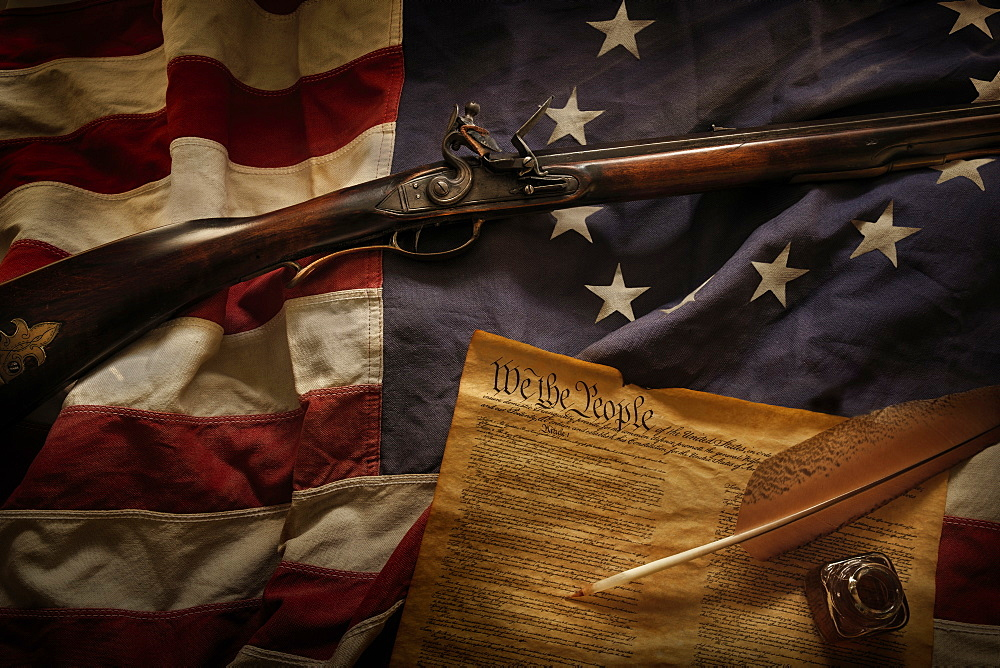 Rifle and US constitution lying on American flag