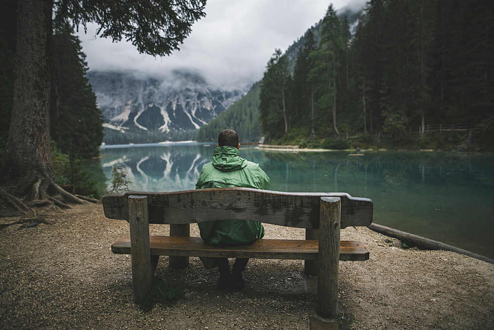 Italy, Man sitting on bench looking at Pragser Wildsee
