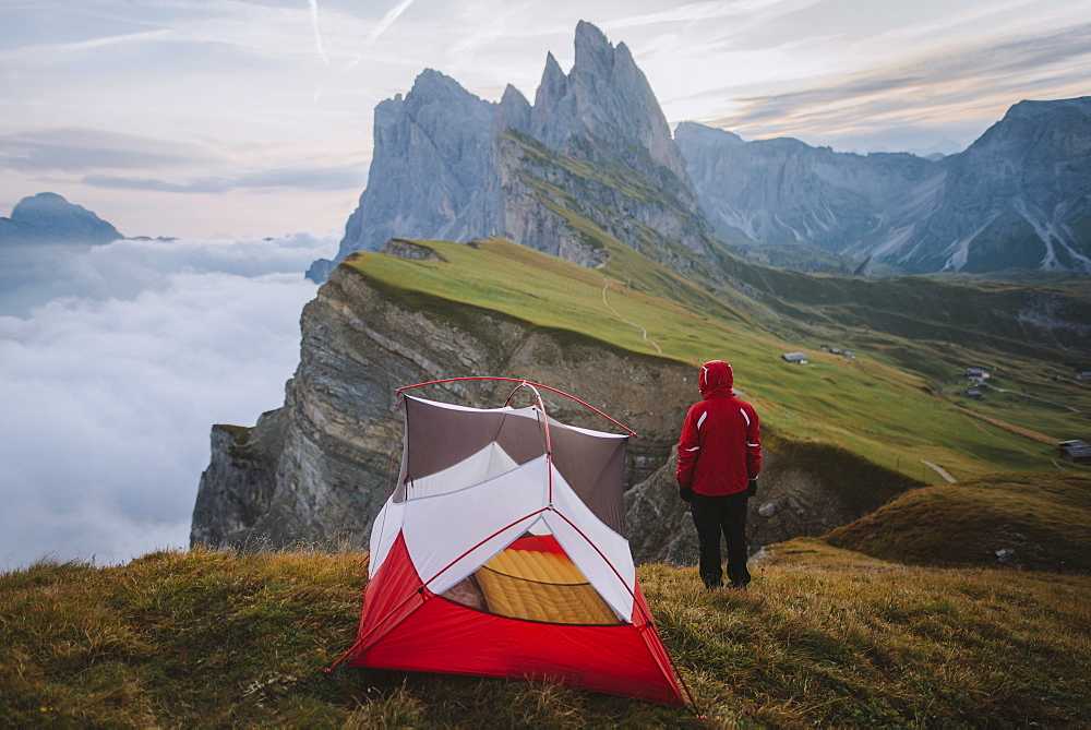 Italy, Dolomite Alps, Seceda mountain, Man standing near tent looking at scenic view of Seceda mountain in Dolomites
