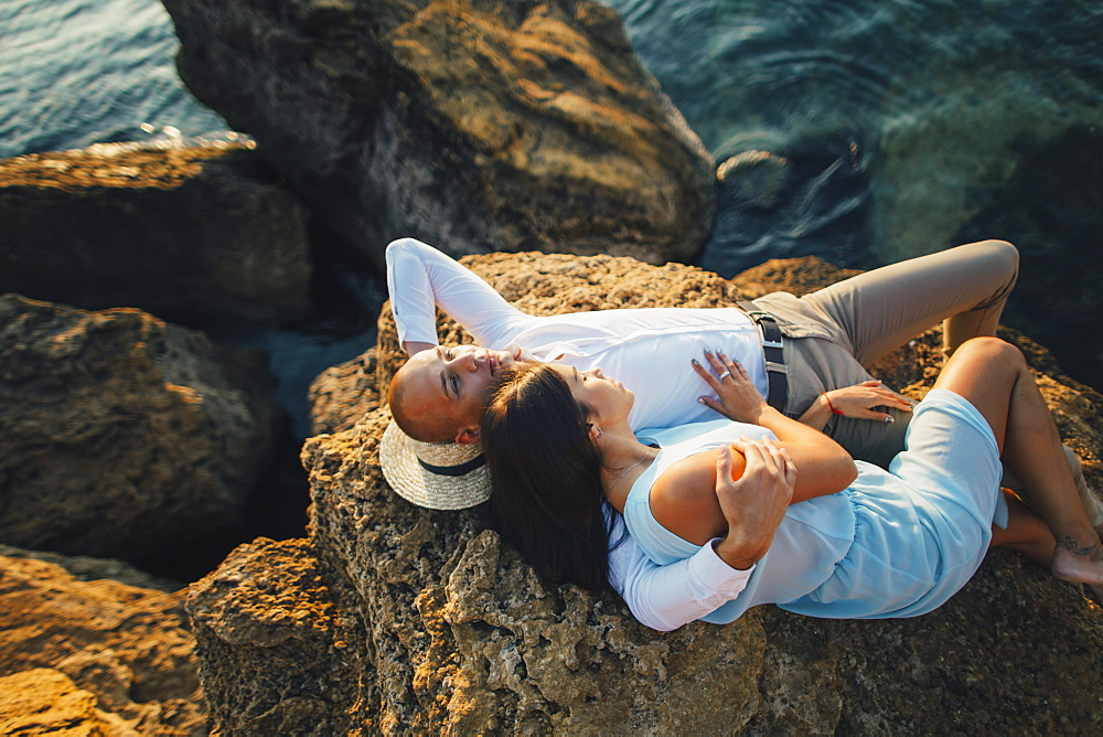 Romantic couple relaxing on rock by sea