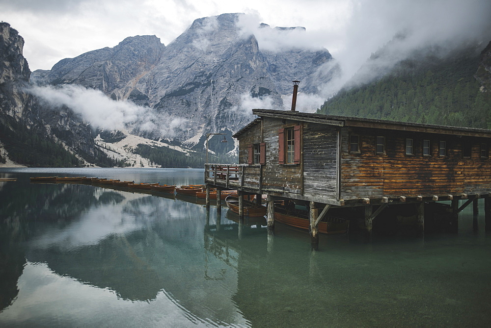 Italy, Wooden hut and boats at Pragser Wildsee in Dolomites