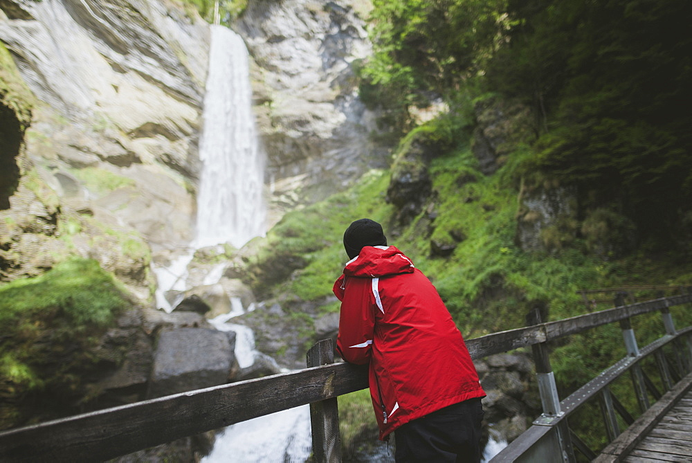 Switzerland, Man looking at Berschner waterfall in mountains - 1178-30147