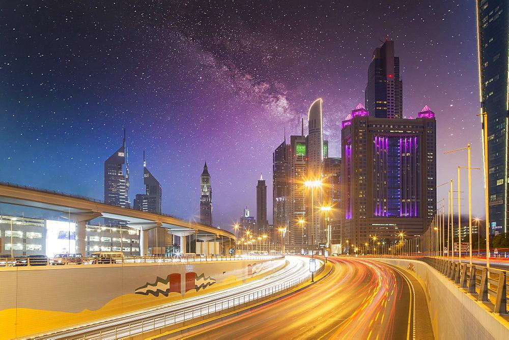 United Arab Emirates, Dubai, Traffic on highway and modern city architecture at dusk