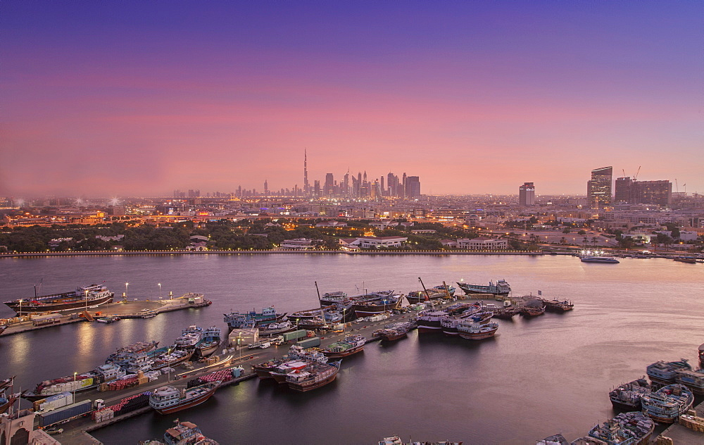 United Arab Emirates, Dubai, Boats on Dubai Creek and skyline at sunset