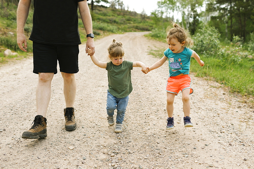 Father and daughters (2-3) holding hands during walk