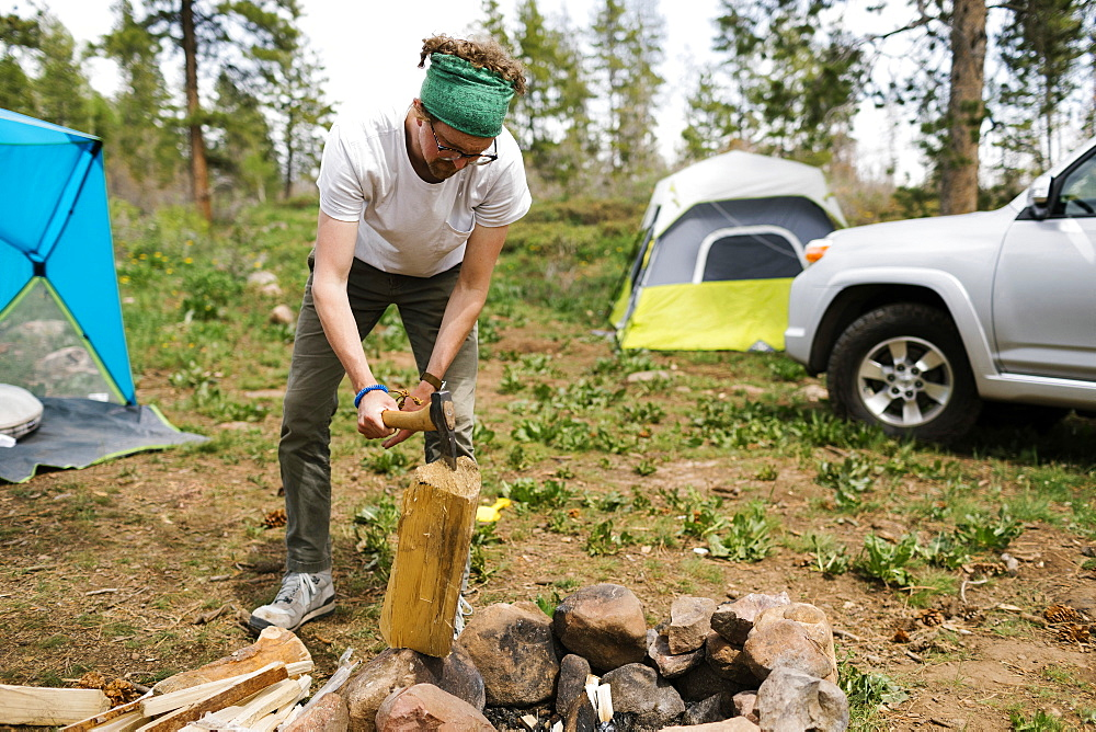USA, Utah, Uninta Wasatch Cache National Forest, Man chopping wood during camping - 1178-30211