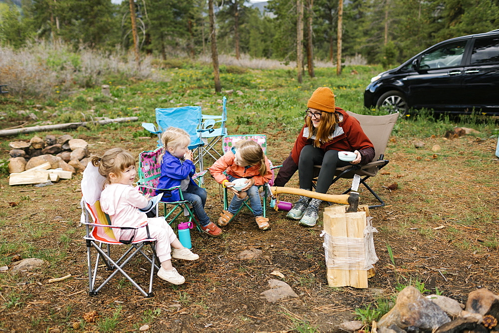 USA, Utah, Uninta Wasatch Cache National Forest, Mother with daughters (2-3, 6-7) eating breakfast during camping