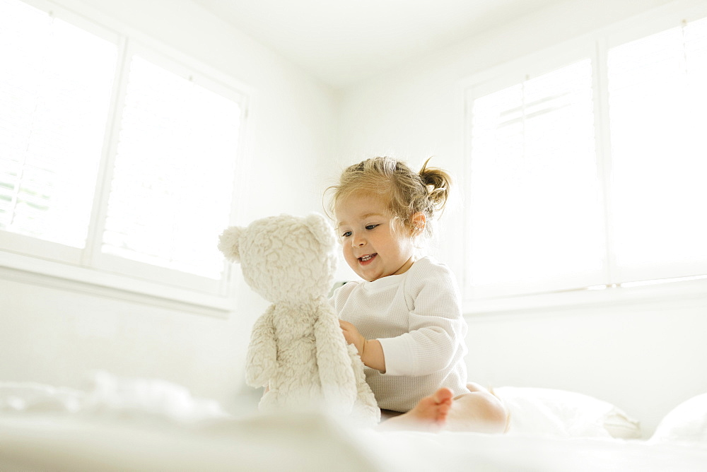 Toddler girl playing on bed with her teddy bear toy - 1178-30228