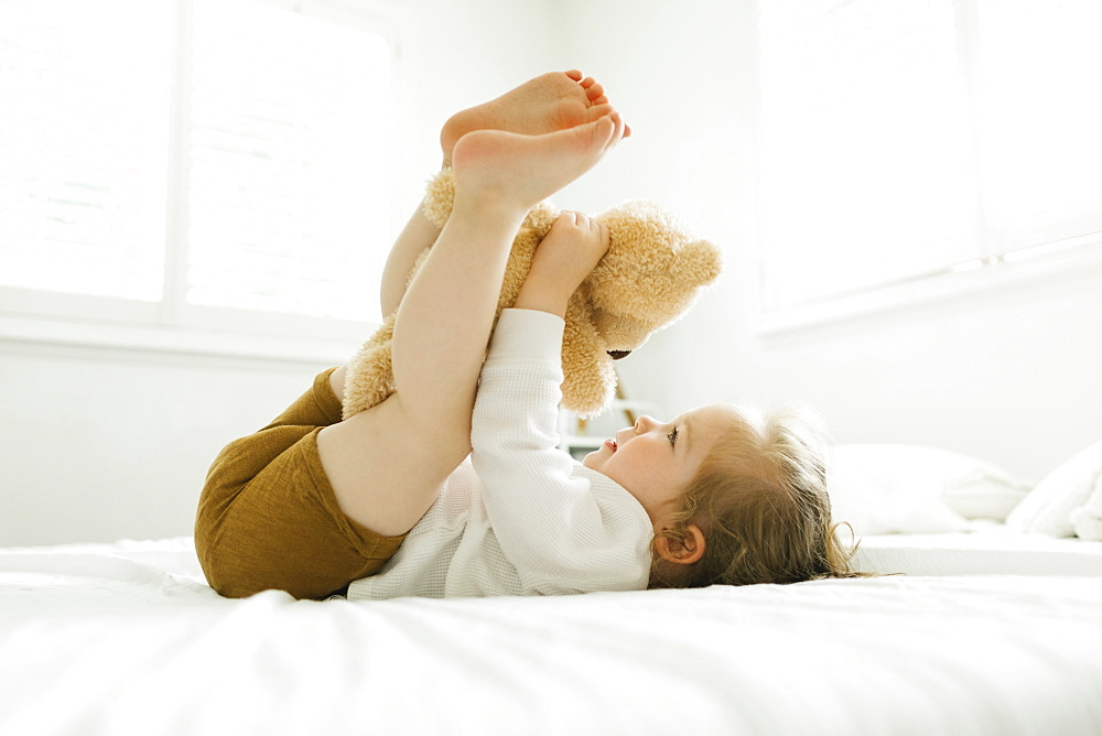 Toddler girl lying on bed with her teddy bear toy - 1178-30229