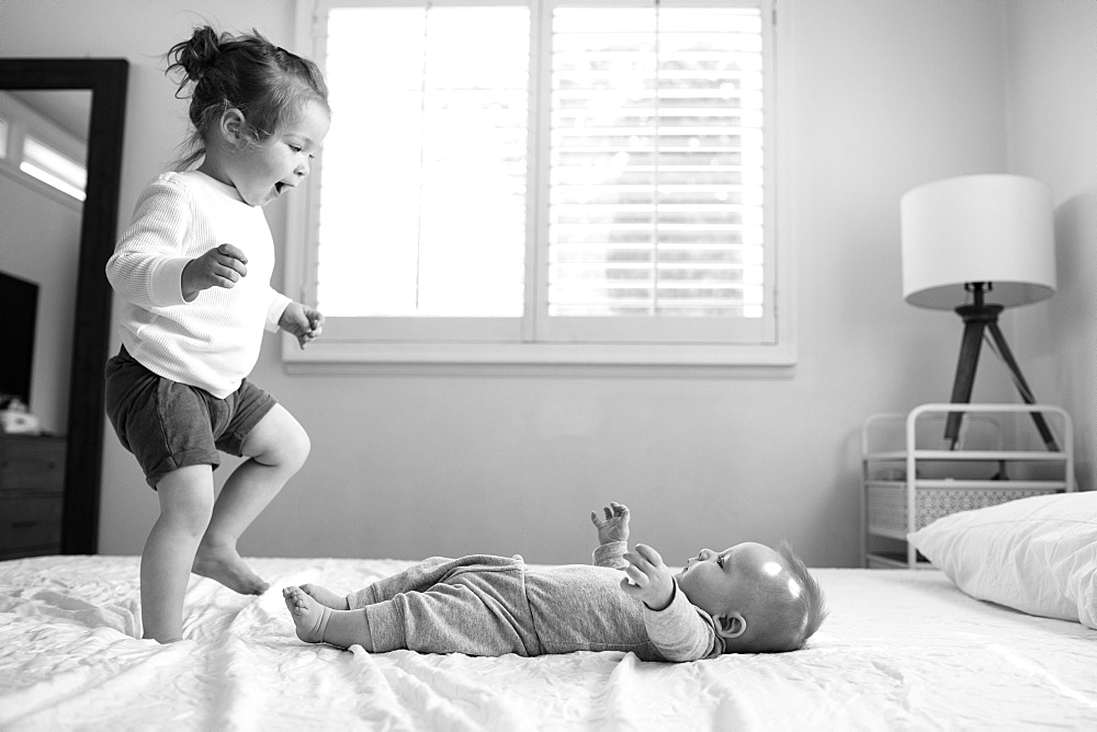 Toddler sister playing on bed with her baby brother
