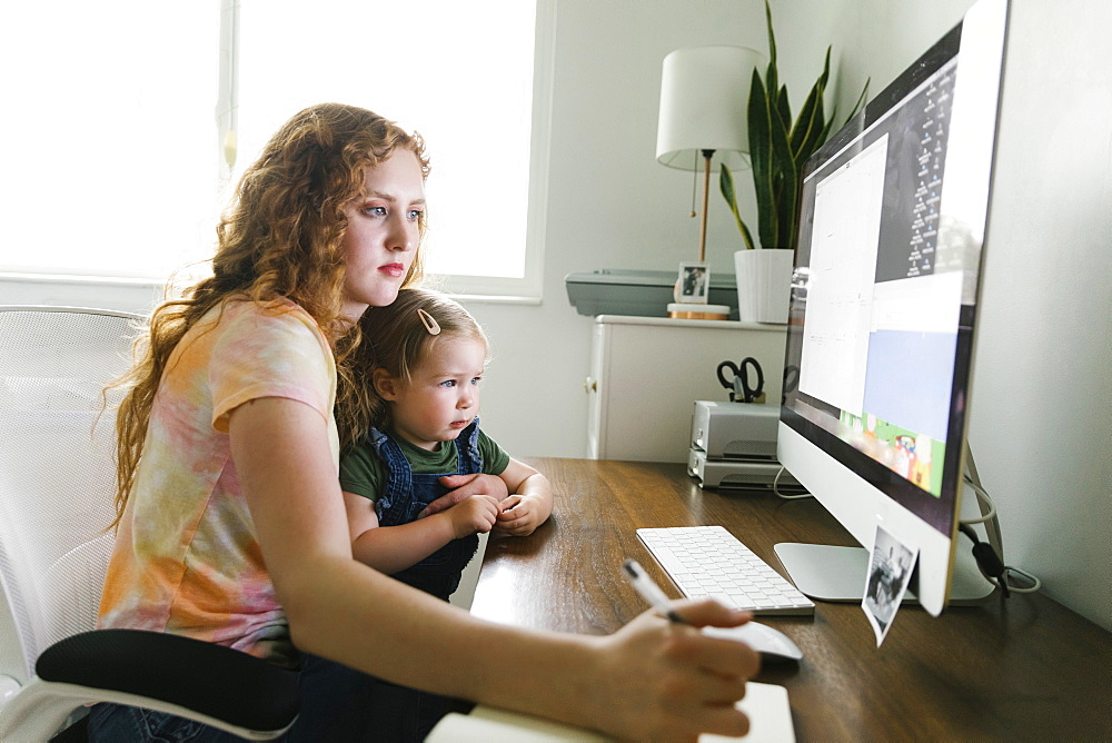 Young mother with her daughter on lap working from home at desk