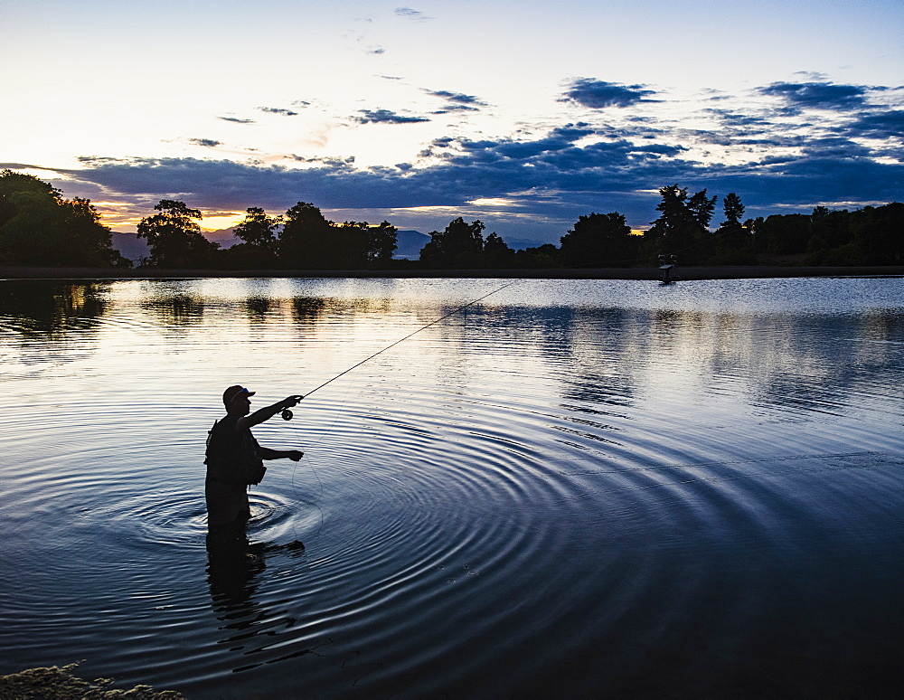 USA, Utah, Salem, Silhouette of man fly fishing in lake at dusk - 1178-30323