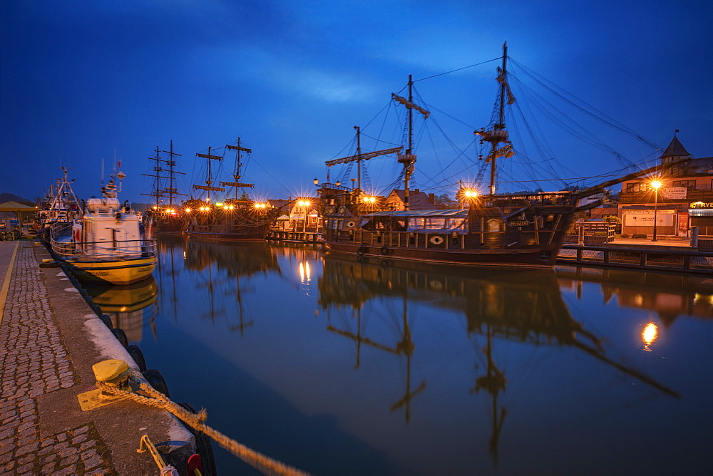 Poland, Pomerania, Leba, Historic tall ships moored at harbour at dusk - 1178-30358