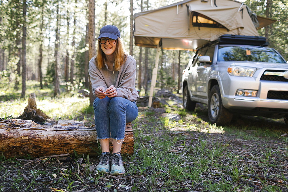 Portrait of smiling woman sitting on log on camping, car with tent in background, Wasatch Cache National Forest