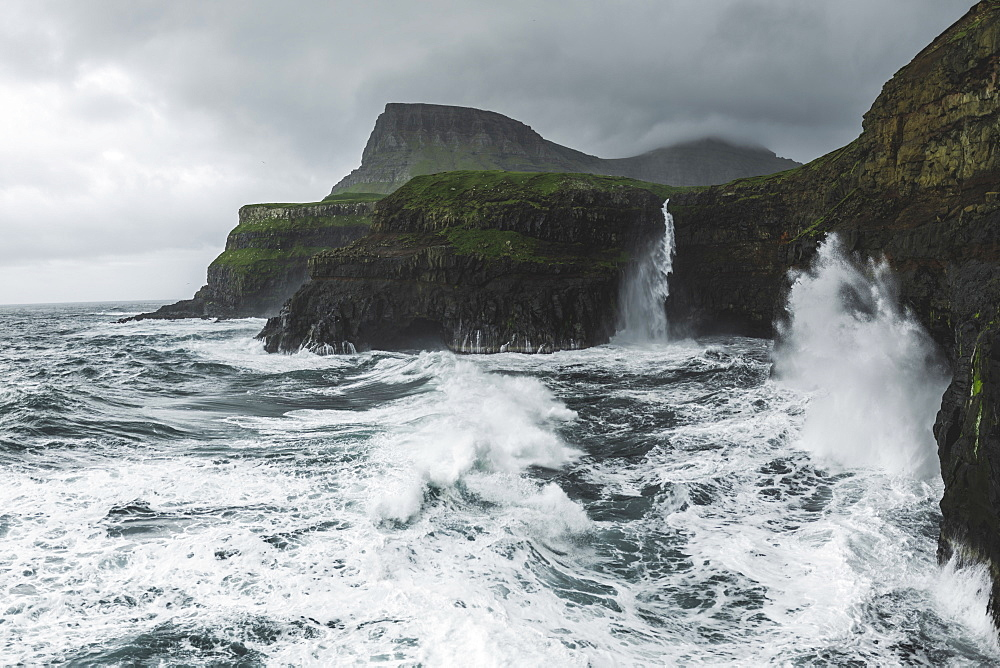 Denmark, Faroe Islands, Gasadalur Village, Mulafossur Waterfalll, Coastline with Mulafossur Waterfall falling into Atlantic Ocean in stormy day - 1178-30559