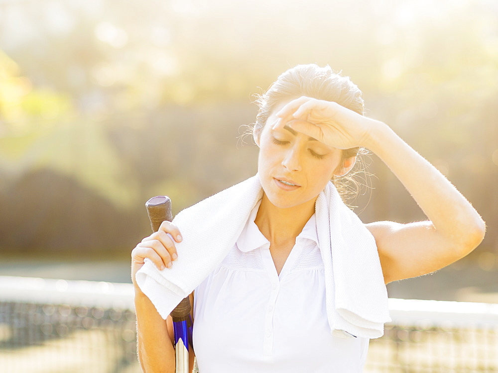 Portrait of young woman with towel and tennis racket wiping forehead with back of hand