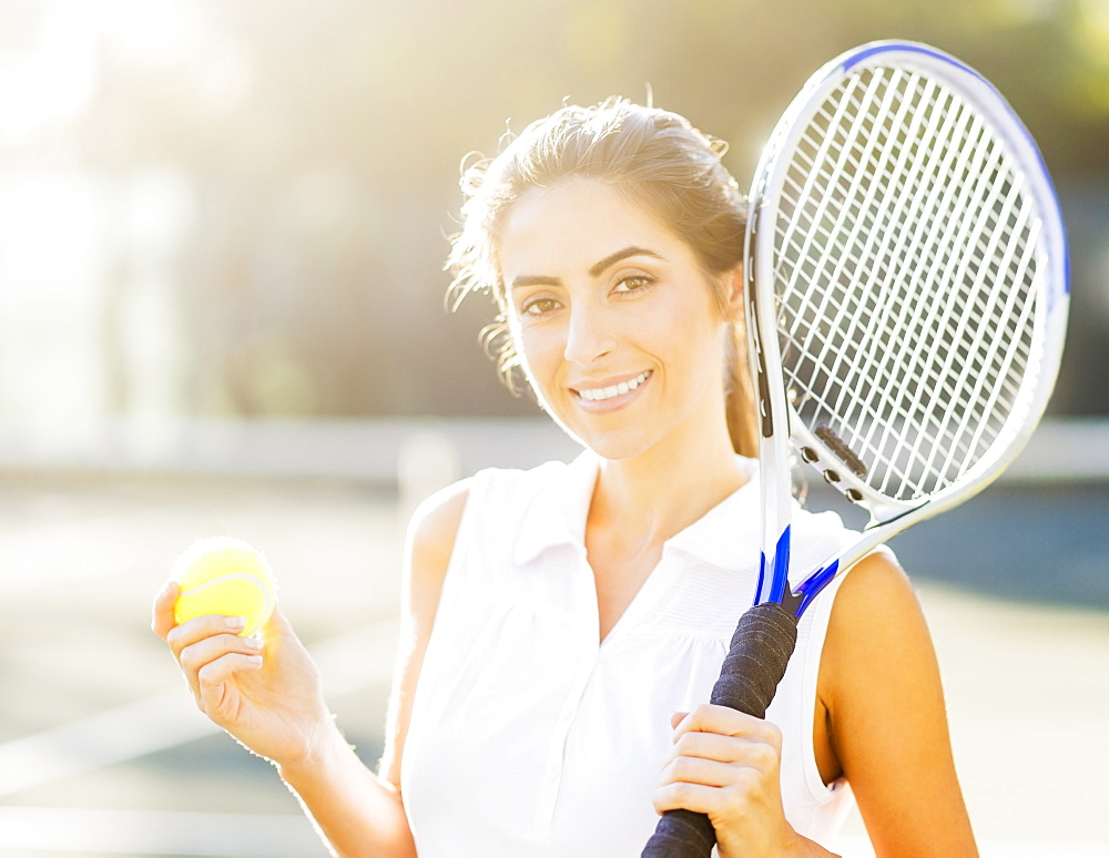 Portrait of young woman holding tennis ball and tennis racket