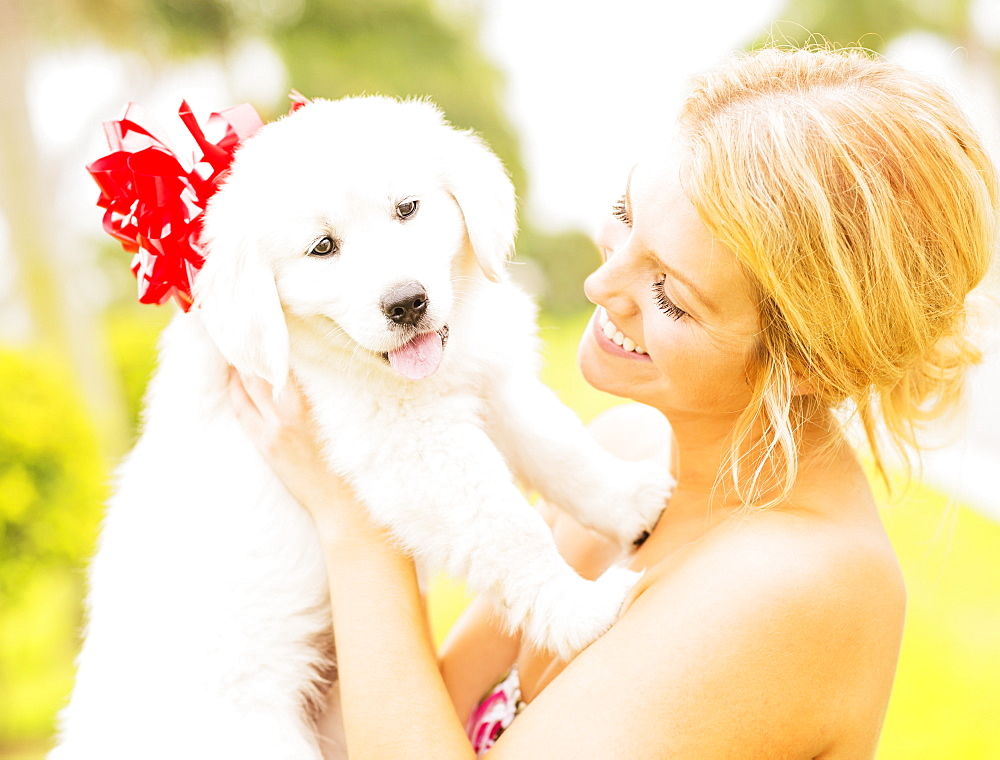 Young woman holding white puppy with ribbon bow, Jupiter, Florida