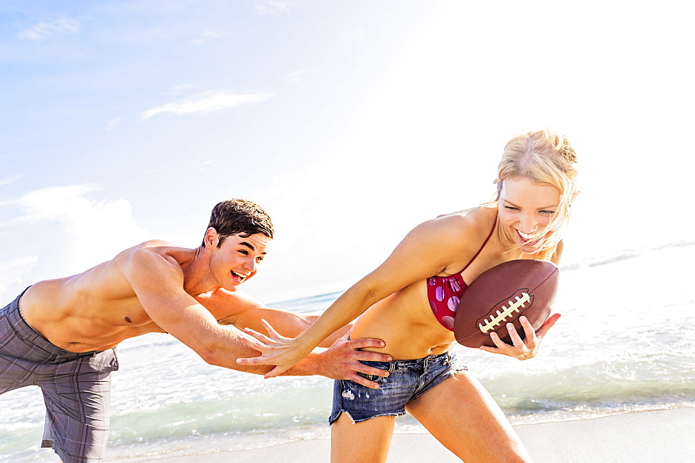 Cheerful young couple playing football on beach, Jupiter, Florida