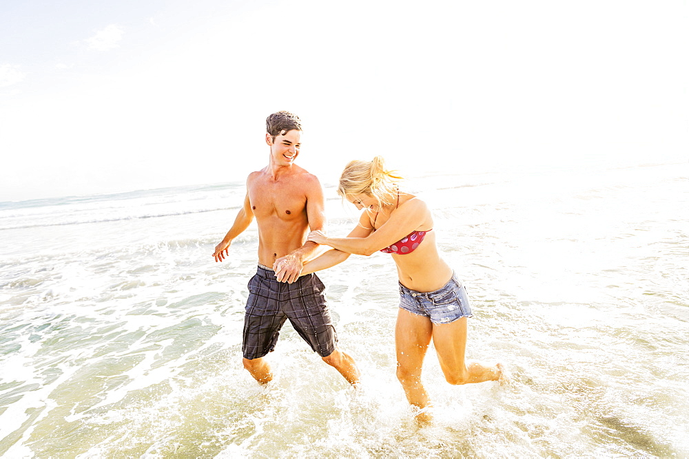 Young couple running in surf holding hands, Jupiter, Florida
