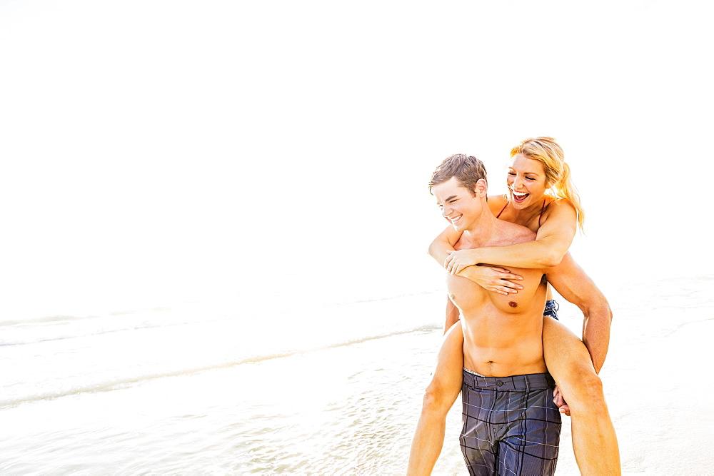 Boyfriend carrying girlfriend piggyback on beach, Jupiter, Florida