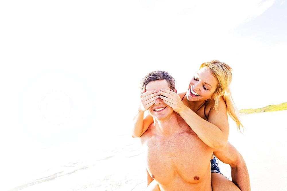 Girlfriend riding piggyback on beach, closing boyfriend's eyes with palms, Jupiter, Florida