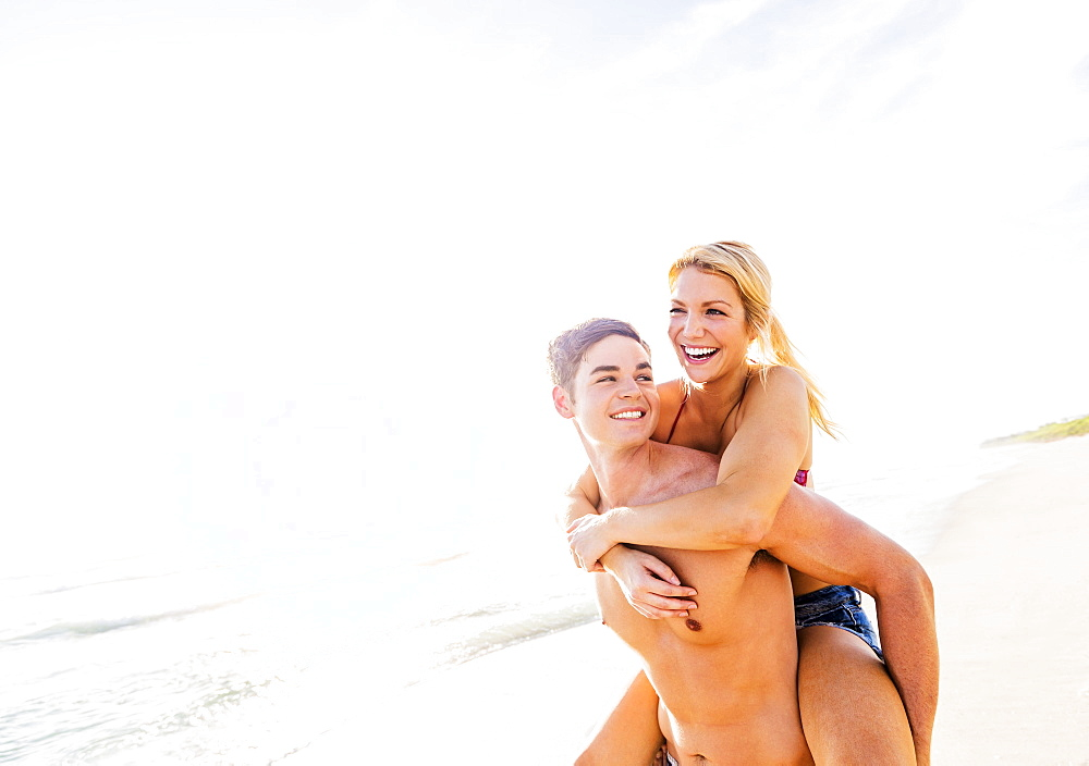 Boyfriend carrying girlfriend piggyback on beach, Jupiter, Florida