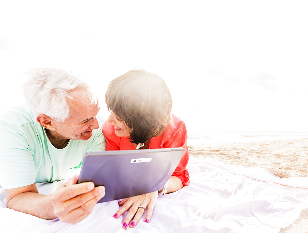 Couple with digital tablet lying on blanket at beach, Jupiter, Florida