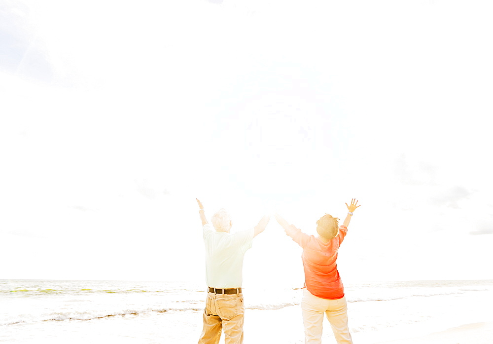 Rear view of couple with arms raised on beach, Jupiter, Florida