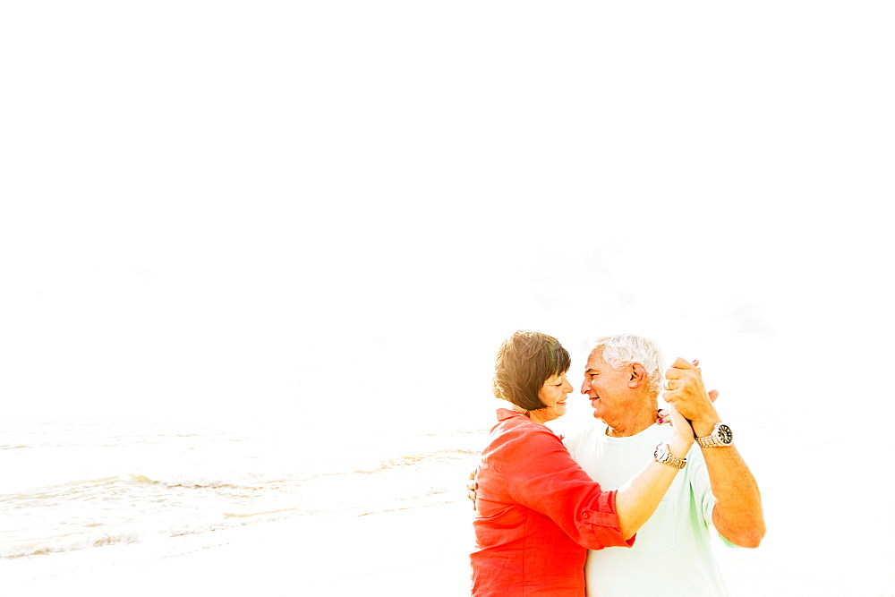 Couple dancing on beach at sunrise, Jupiter, Florida