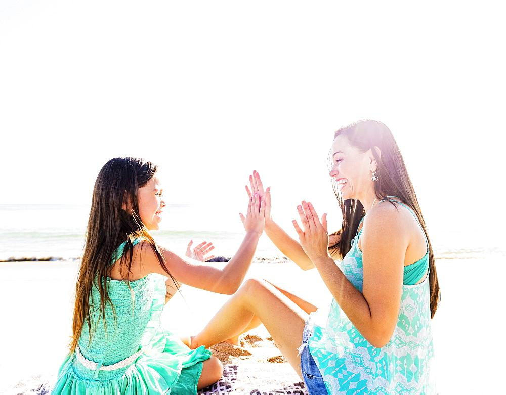 Mom and daughter (6-7) playing patty cake on beach, Jupiter, Florida