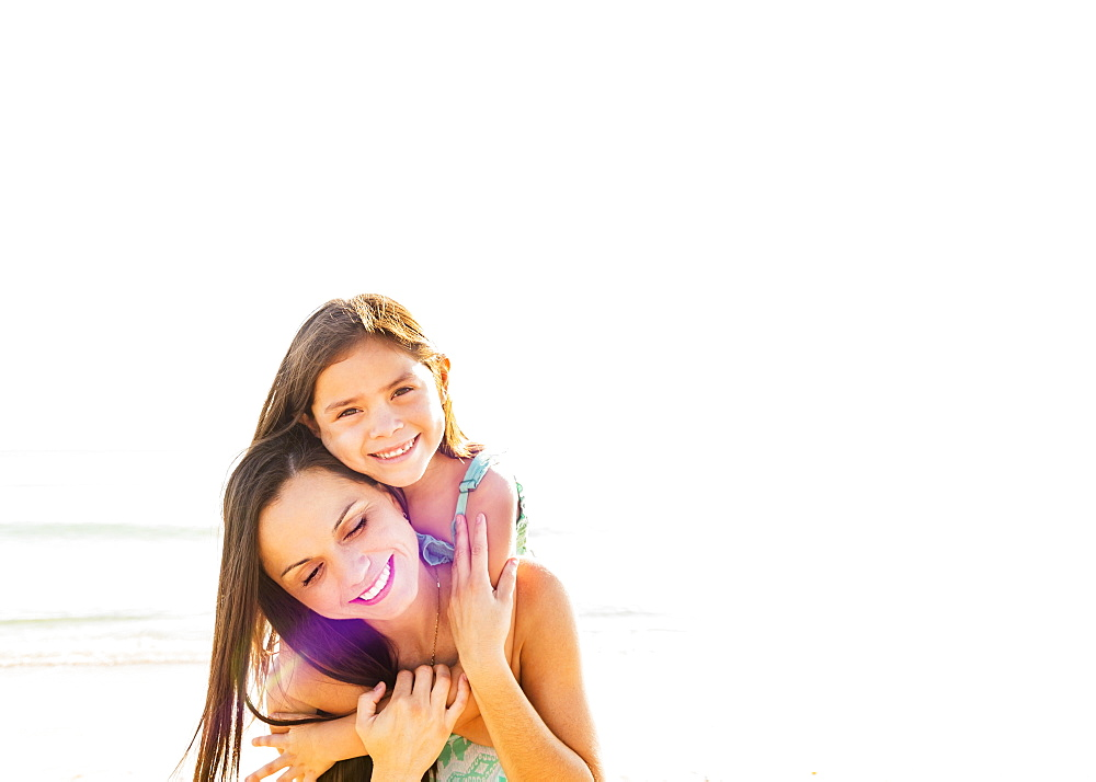 Portrait of smiling girl (6-7) with her mom on beach, Jupiter, Florida
