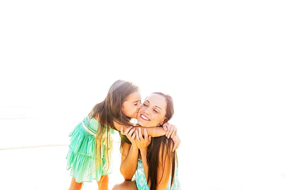 Girl (6-7) kissing her mother on cheek on beach, Jupiter, Florida