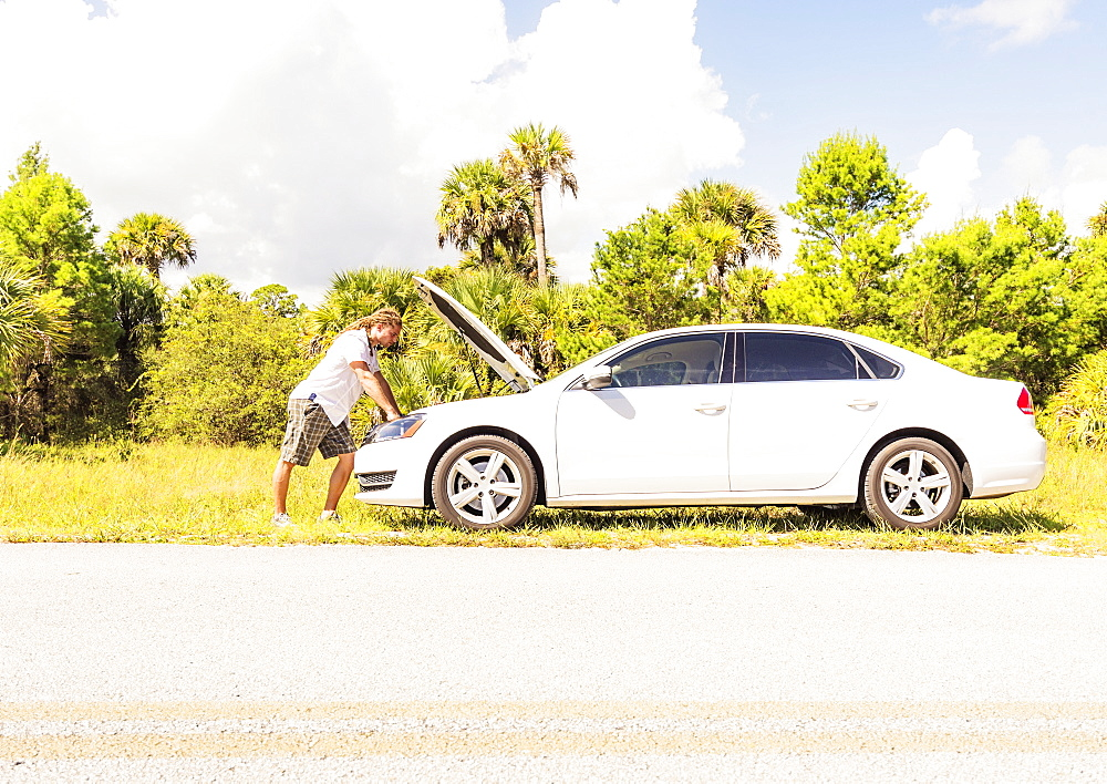 Young man looking at car engine, Tequesta, Florida