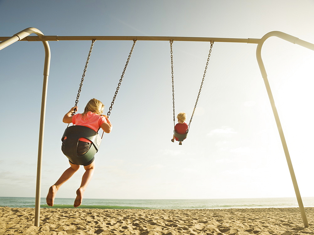 Girl (4-5) and boy (2-3) swinging on beach, San Clemente, California