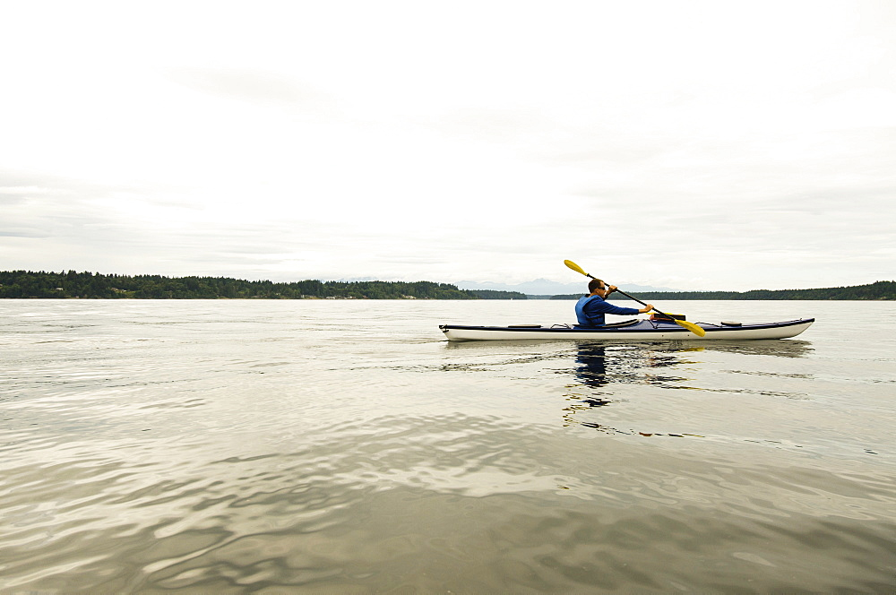 Man kayaking on lake, Olympia, Washington, USA
