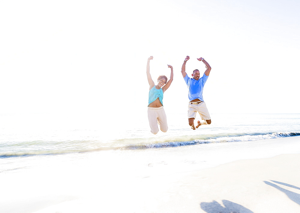 Mature couple jumping in sea with arms raised
