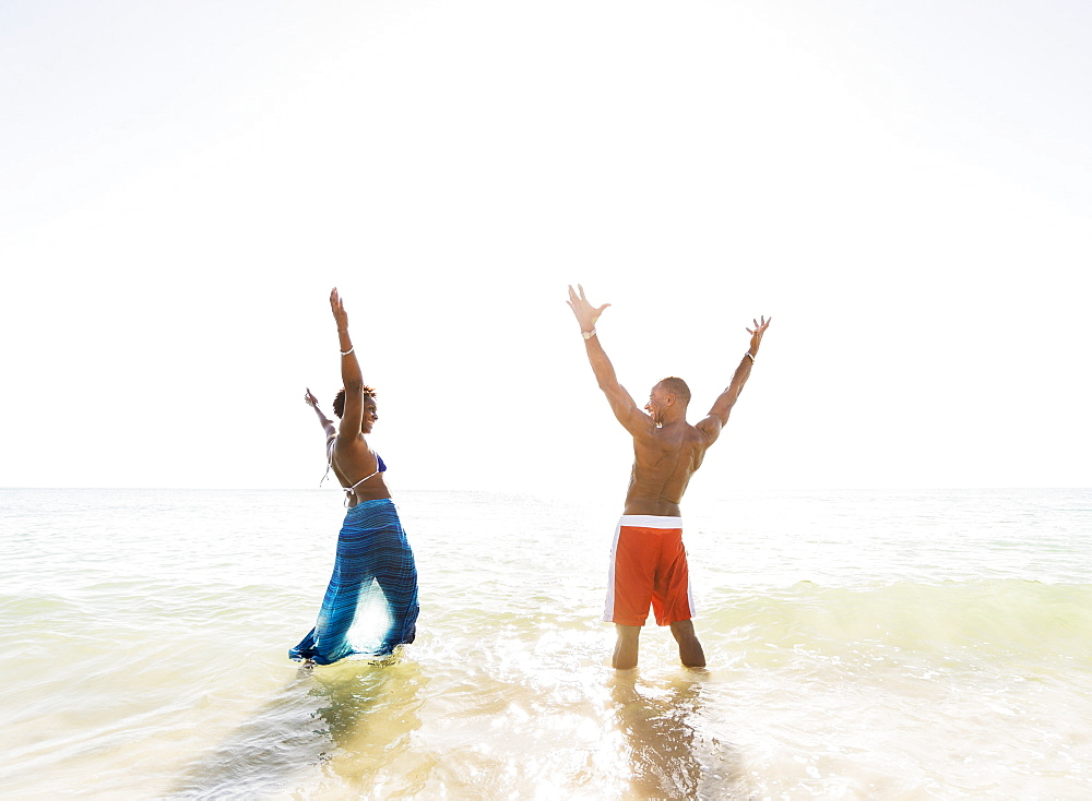 Mature couple standing in sea with arms raised
