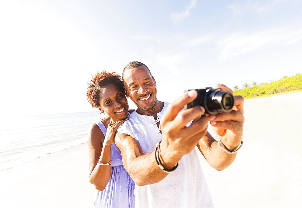 Man and woman photographing on beach, Jupiter, Florida