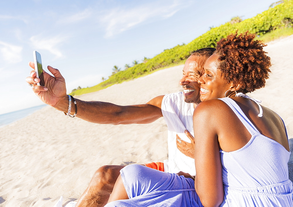 Man and woman photographing self on beach, Jupiter, Florida