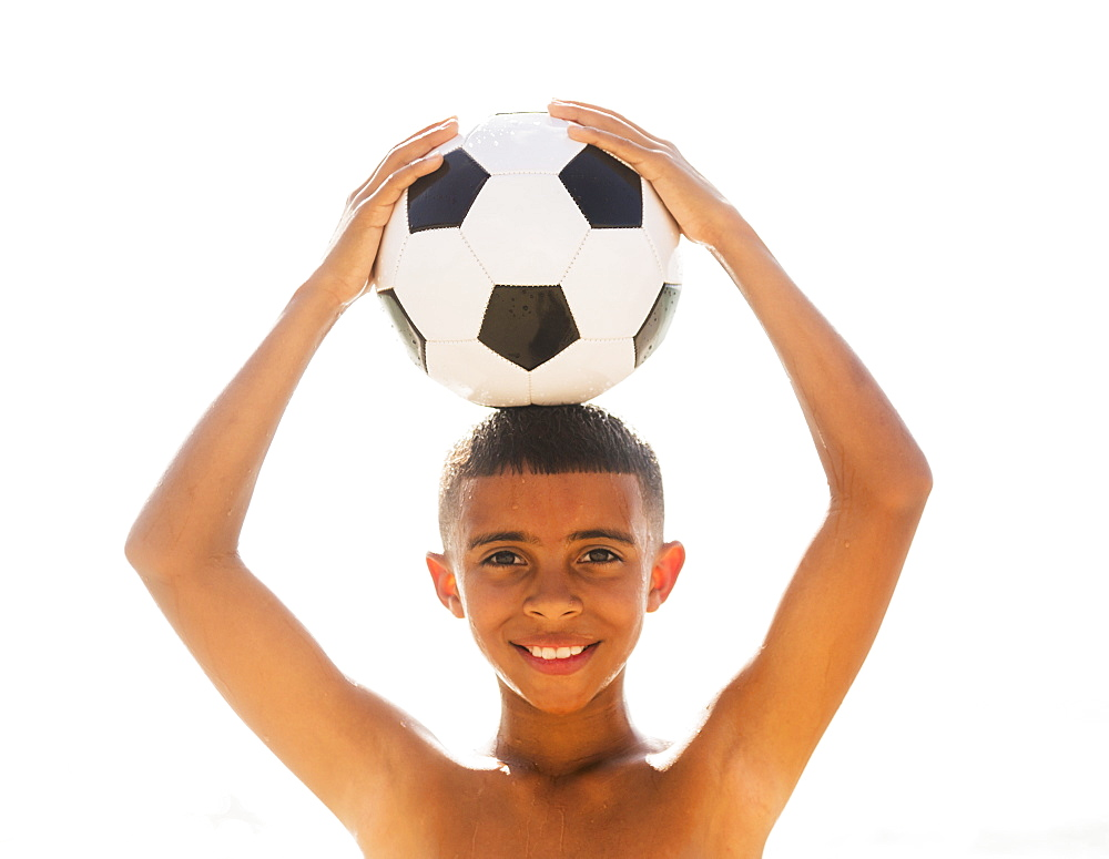 Boy (10-11) holding soccer ball on head