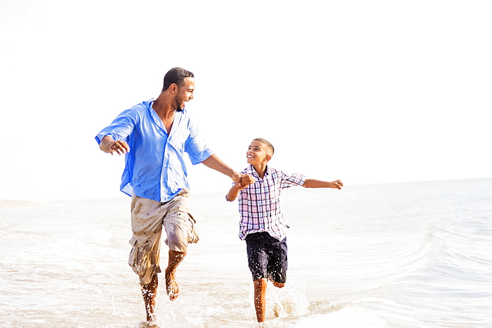 Father and son (10-11) running on beach