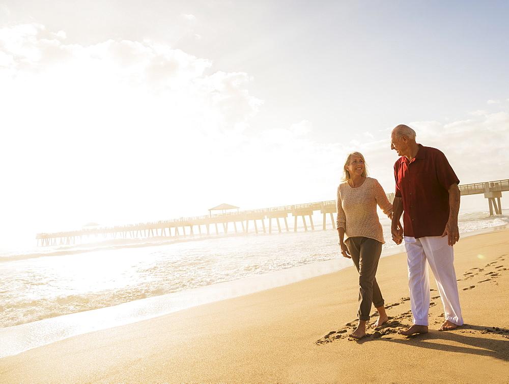 Senior couple walking on beach, Jupiter, Florida
