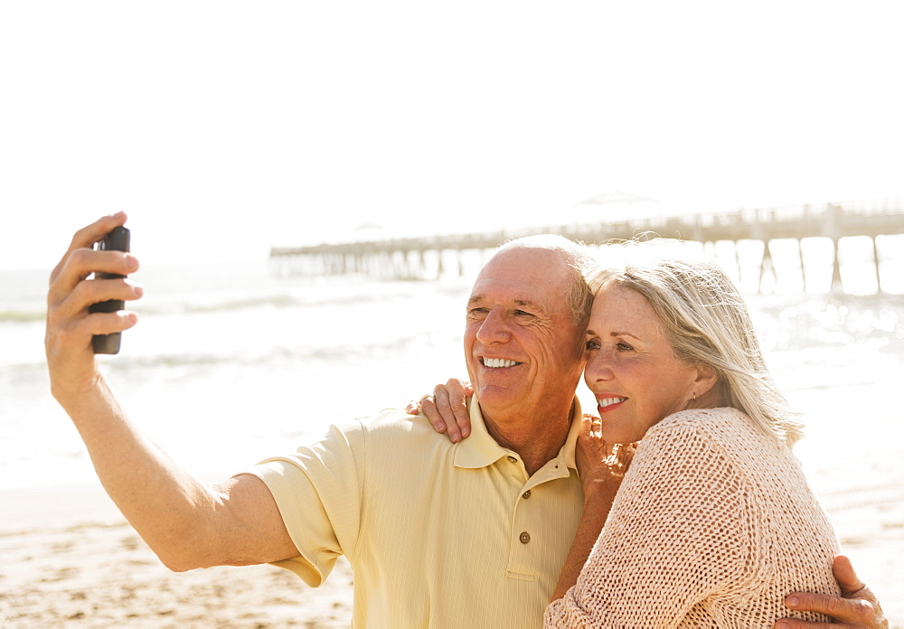 Senior couple taking picture of themselves on beach, Jupiter, Florida