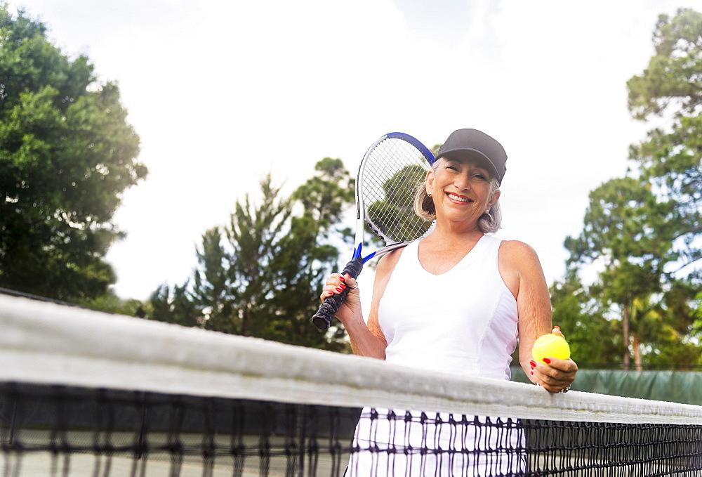 Portrait of senior woman on tennis court, Jupiter, Florida