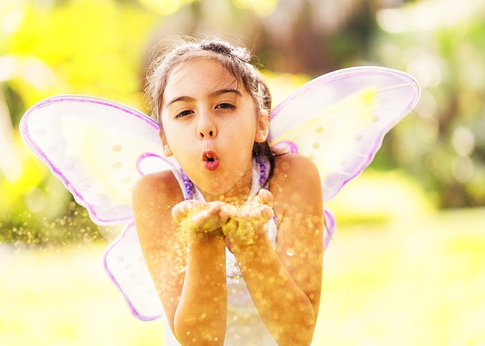 girl (8-9) blowing fairy dust