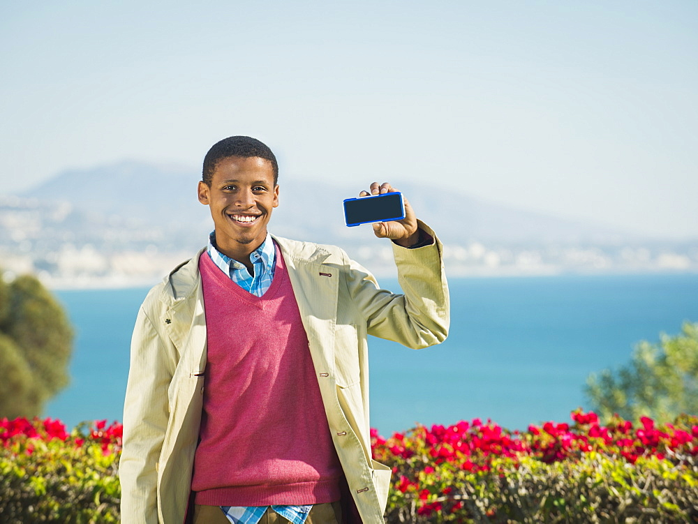 Portrait of smiling man holding smartphone, Dana Point, California