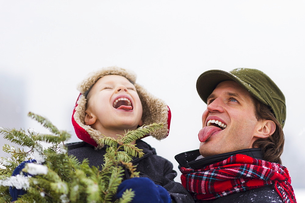Father and son (6-7) catching snowflakes on tongue