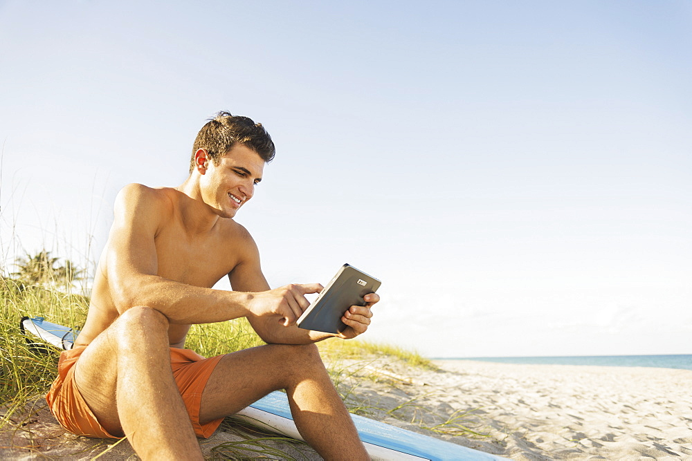 Young man sitting on beach with surfboard and digital tablet, Jupiter, Florida, USA