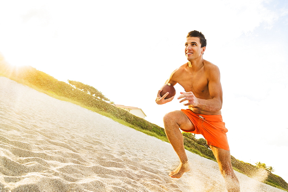 Young man playing football on beach, Jupiter, Florida, USA